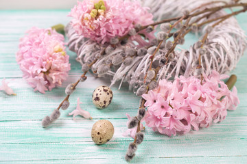 Quail eggs, willow  branches and  pink hyacinths flowers on wood