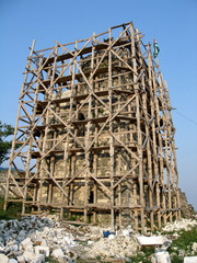 Scaffolding covering a old tower under restoration. Abkhazia