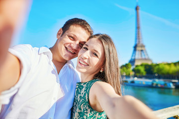 Young romantic couple taking funnyselfie with mobile phone near the Eiffel tower in Paris, France