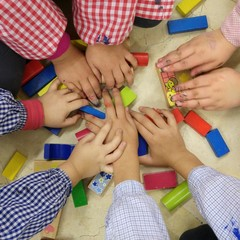Manos de niños jugando con madera de colores