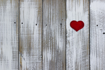 Red heart hanging on whitewash rustic fence