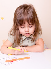 delighting drawing girl at the desk in preschool