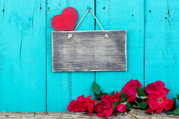 Blank sign and red roses by wood background