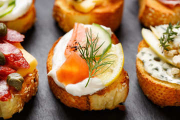 Small canape with grilled baguette with the addition of  cream cheese, smoked salmon, cucumber, lemon and fresh dill on black background