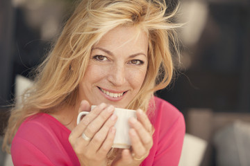 Blonde adult woman drinking coffee