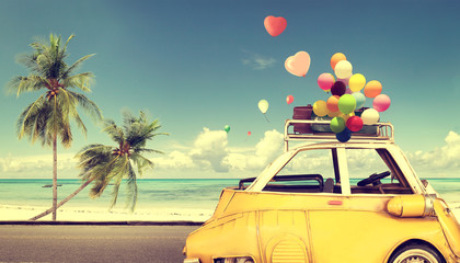 Wall Mural - Vintage yellow car with heart colorful balloon on beach blue sky - concept of love in summer and wedding. Honeymoon trip