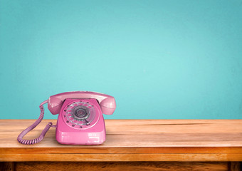 Old retro pink telephone on table with vintage green pastel background