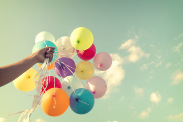 Wall Mural - Girl hand holding colorful balloons. happy birthday party. vintage filter effect