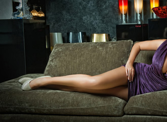 Long legs woman laying on sofa, boudoir shot. Sexy female on high heels shoes resting on couch. Erotic pose. Sensual girl wearing short tight fit dress posing provocatively indoors
