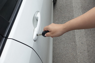 woman hand holding car keys to unlock or lock the white car