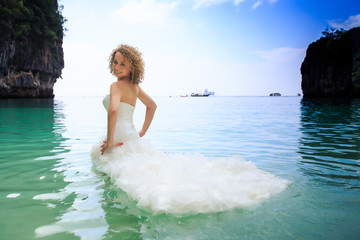 side view blonde bride in fluffy dress in shallow azure sea