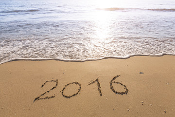 2016 written on a sandy beach with bright sun
