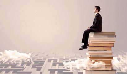Businessman sitting on books in labirynth