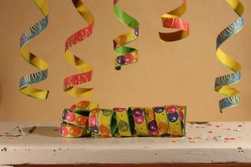Luftschlangen und Konfetti auf einem kleinen weißen Holztisch