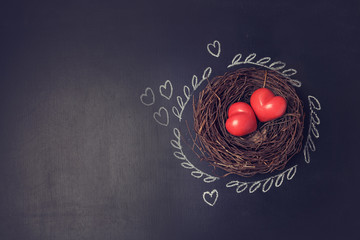 Valentine's day background with hearts in bird nest over chalkboard. View from above