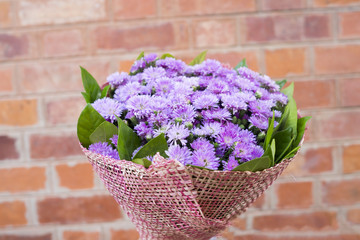 Bouquet of purple flowers in vintage brown brick as background (Selective focus)