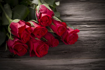 Red roses on old wooden table.