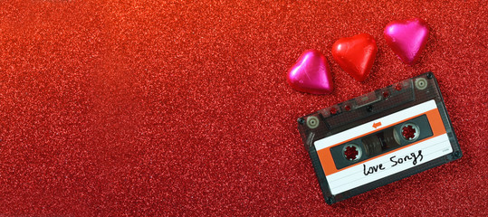 website banner image of colorful heart shape chocolates and audio cassette on glitter background. valentine's day celebration concept. retro toned and filtered