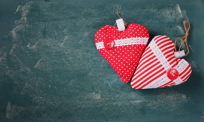 top view image of fabric hearts on blackboard background. valentine's day celebration concept
