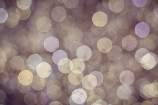 Light blurred background with white bokeh lights on it. Festive holiday theme with copyspace