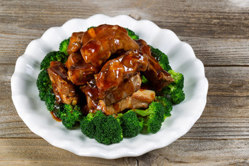 Super saucy barbecued ribs with vegetables on white plate