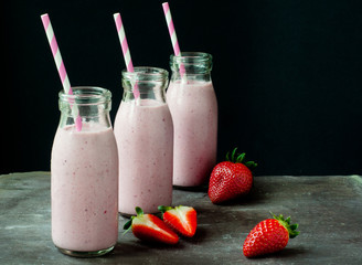 Smoothie milkshake made from fresh strawberry blended with kefir yogurt. Served in bottle style glasses and with fresh strawberries. Served on a stone slate table with colorful stripy straws.