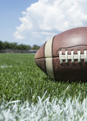 Closeup photo of a football resting on an outdoor field