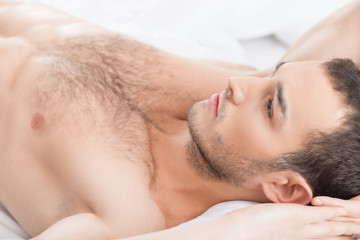 Cheerful fit guy is resting in bedroom
