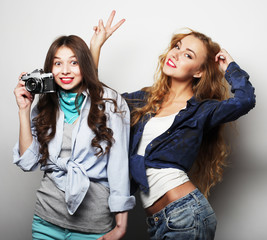 Happy girls friends taking some pictures, with camera