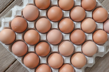 Eggs in paper tray on wood background