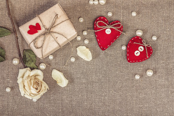 gift box with a white dry rose and two red hearts on sacking, co