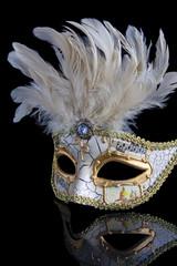 Opera masker in off-white en goud, weerspiegeld op een zwarte ondergrond.