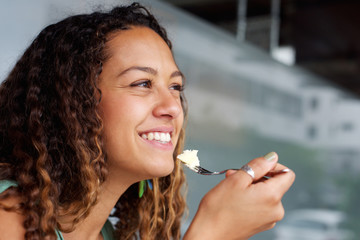 Happy young woman eating cheese cake