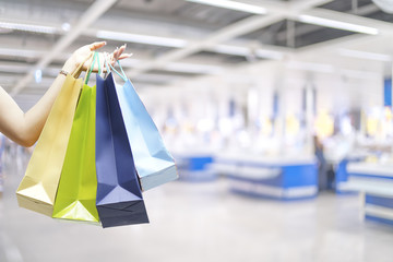 Hand holding shopping bags with blurred of cashier store backgro