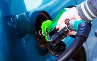 man pumping gasoline fuel in car at gas station. transportation concept