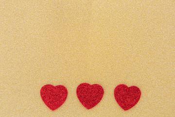 drei Herzen auf goldenem Hintergrund