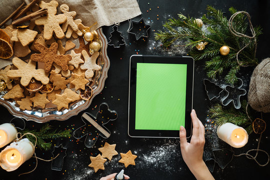 woman with tablet pc computer making gingerbread houses at home