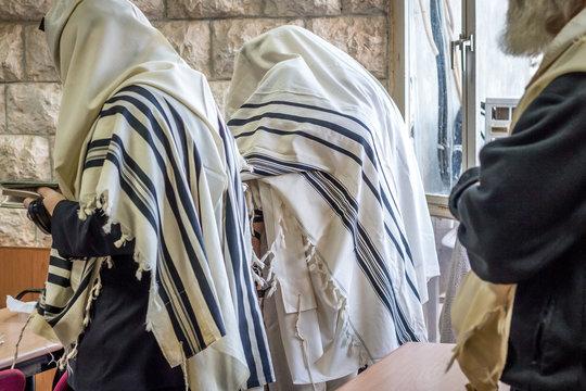 Jewish men praying in a synagogue with Tallit