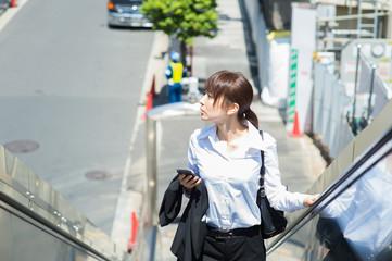 移動中の若い日本人ビジネスウーマン