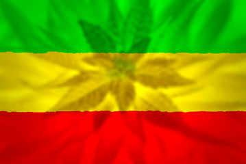 Cannabis bud on grunge rastafarian flag.
