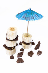 Chocolate tower of banana with umbrella and cut pieces of chocolate and orange isolated on white