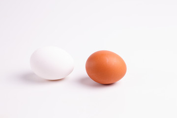 Brown and white chicken eggs lying on a white table.