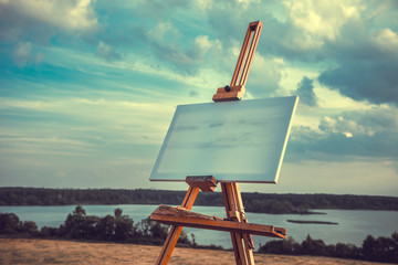 Blank canvas rests on a easel on lake landscape, retro styled ph