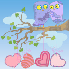 Love owls sit on a tree branch on blue sky background