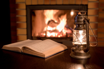 Open book by the Fireplace with kerosene lamp.