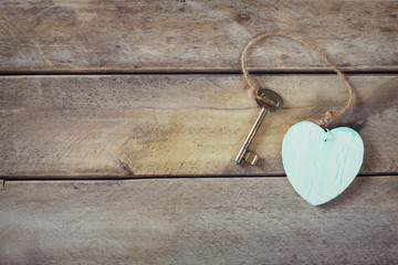 top view of old vintage key with a wooden heart on wooden background. retro filtered and toned