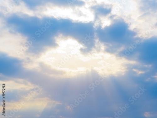 Wall mural sun rays shine through the clouds