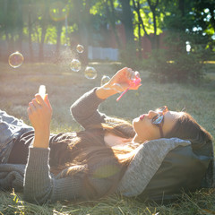 Young woman blowing soap bubbles outdoor in fall park. Image ton