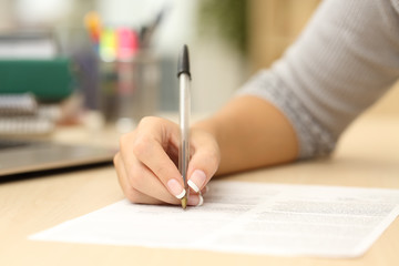 Woman hand writing or signing in a document