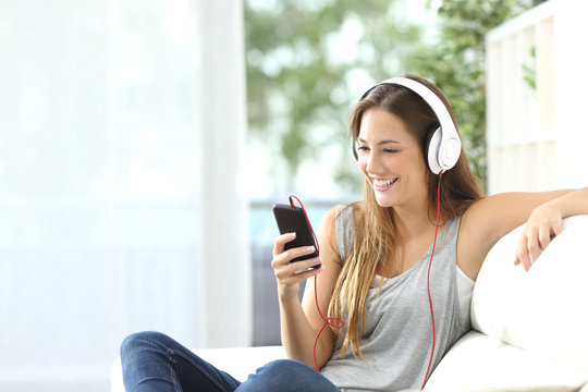 Happy girl listening to music from mobile phone